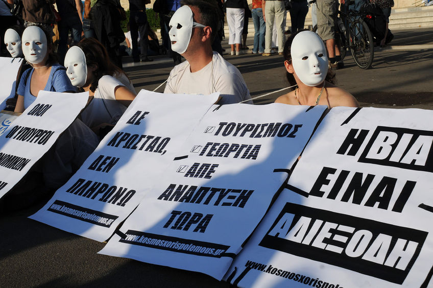 52639633 - athens, greece - may 9, 2010: students wearing white masks protest in the capital of greece athens outside the parliament building against unpopular eu-imf austerity deal