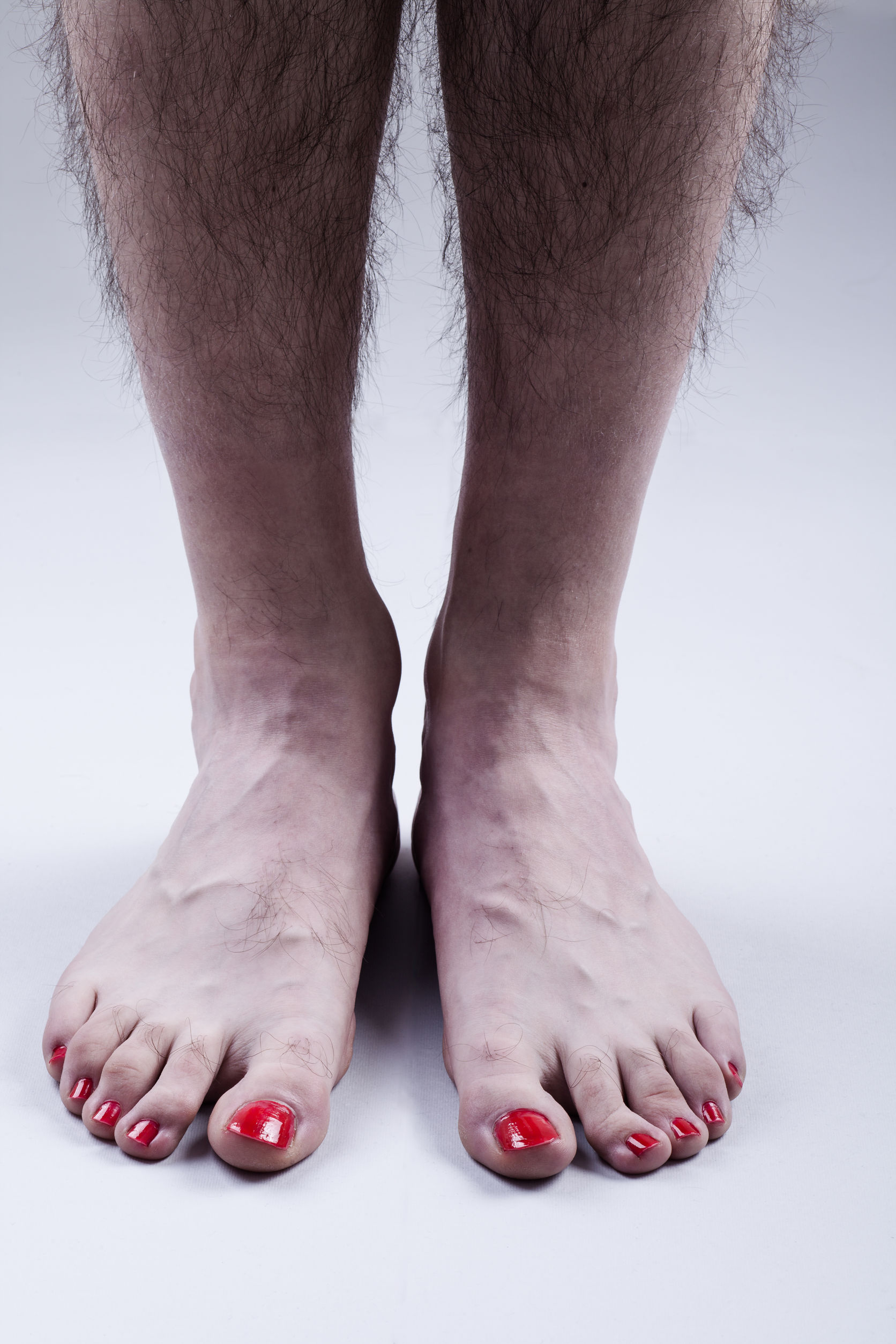 37878915 - man's feet with red nail polish and hairy legs on bright gray background